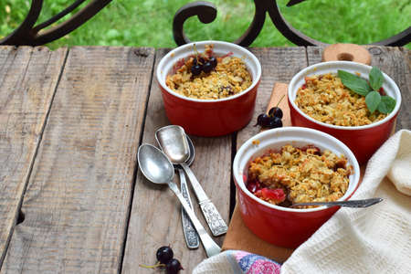 Fruits casserole or crumble with apples and berries in brown cup ramekin on wooden background. Copy space. Photographing with natural light.