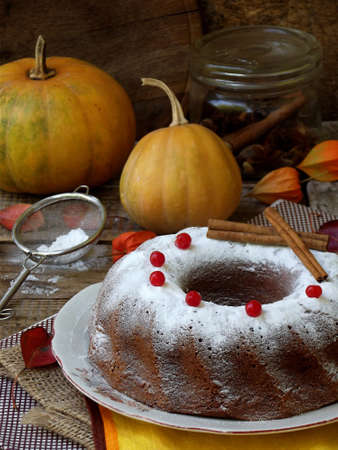 Pumpkin Bundt cake with cranberries and spices sprinkled with powdered sugar on wooden background. Homemade autumn baking