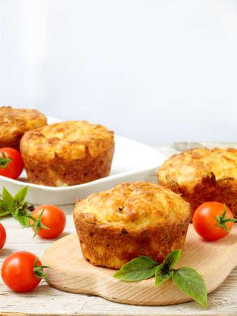 塩味のスナック チーズ、トマトとバジルのセレクティブ フォーカスのマフィンをケーキします。