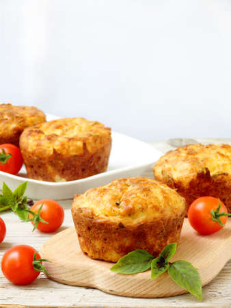 salty snack cakes muffins with cheese, tomatoes and basil - selective focus