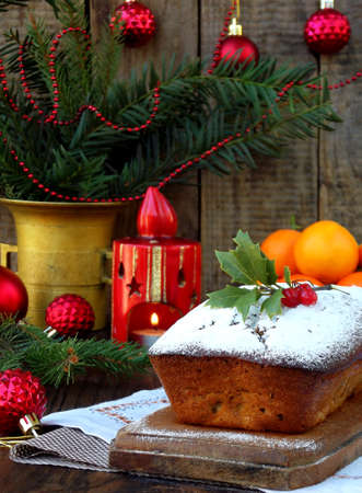 Traditional Christmas fruit cake decorated with powdered sugar and Xmas decorations, candle. copy space. style rustic.