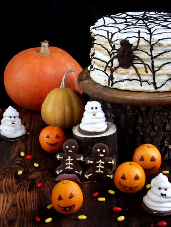 Funny delicious composition for Halloween with cake, biscuits, marshmallow and mandarins on the table. Sweets in the form of ghosts, skeletons, spiders and pumpkin jack. Stock Photo