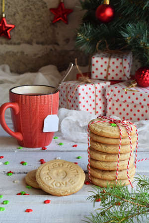Christmas and new year holiday celebration concept background. Mug of tea, homemade nut cookie, shortbread, xmas tree decoration on wooden table.