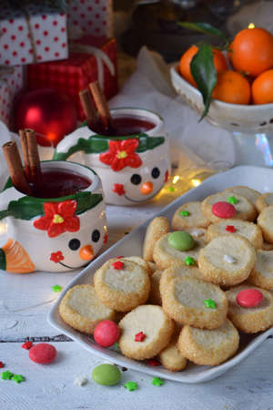Christmas and new year holiday celebration concept background. Mug of mulled wine with spices, homemade nut cookie, shortbread, xmas tree decoration on wooden table.