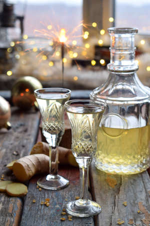 Homemade ginger tincture or ale on wooden background. Rustic style. Spice yellow liqueur in a glass. Alcohol drink