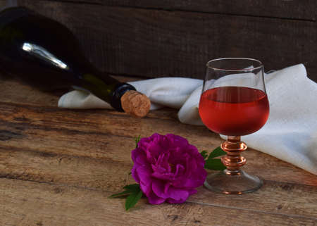 A glass of red wine, bottle and rose on rustic wood table. Valentines Day, Birthday, Mother's day, March 8, Wedding still life. Concept greeting card. Copy space for text.