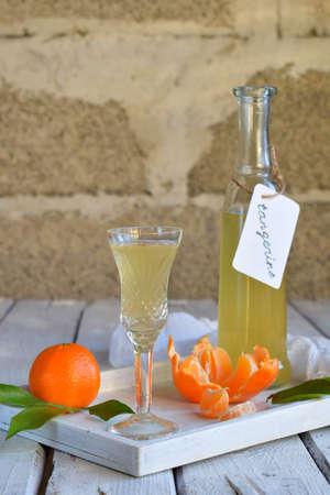 Tangerine liqueur in glass. Delicious yellow alcohol drink. Mandarine liquor. Glass bottle, shot and citrus fruit. Copy space.