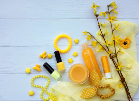 Set of yellow accessories for young girl or teenager. Nail polishes, lipstick, hair clips, bands, beads, bracelet, perfume and flowers. Spring beauty still life. Copy space. Top view.
