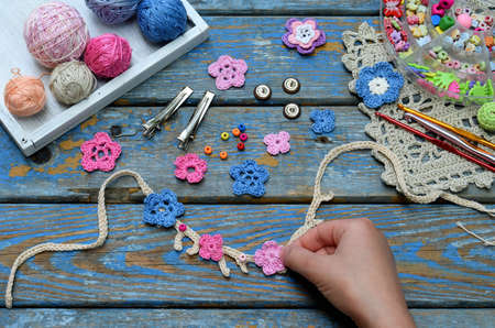 Needlework accessories for creating crocheted jewelry. Step 2 - sew crocheted flowers to bracelet or chain. DIY project. Small business. Income from hobby.
