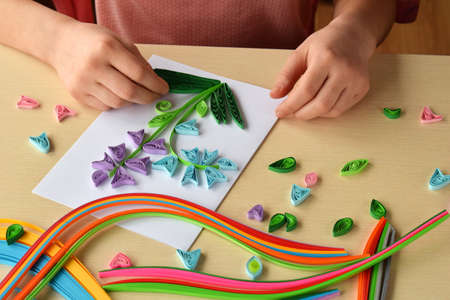 Quilling technique. Girl making decorations or greeting card. Paper strips, flower, scissors. Handmade crafts on holiday: Birthday, Mother's or Father's Day, March 8, Wedding. Children's DIY concept