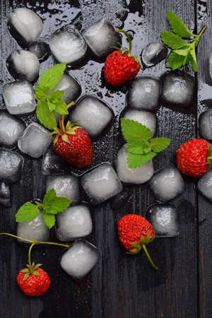 Ice cubes, strawberries and mint leaves on a black wooden background. Food background. Stock Photo