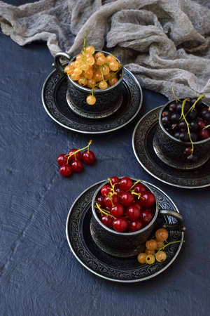 Composition of fresh ripe berries: red, black and white currants on a dark gray concrete background. Dark photo. Photographing in natural light. Space for your text