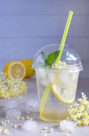 Homemade elderflower lemonade with lemon and elderberry flowers in plastic cup with sphere dome cap and cocktail tube. Elderflower cordial. Summer cold drink. Stock Photo
