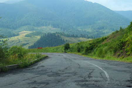 Damaged road in Carpathian mountains, in the Ukraine. Cracked asphalt blacktop with potholes. Summer landscape, forest, sky. Stock Photo