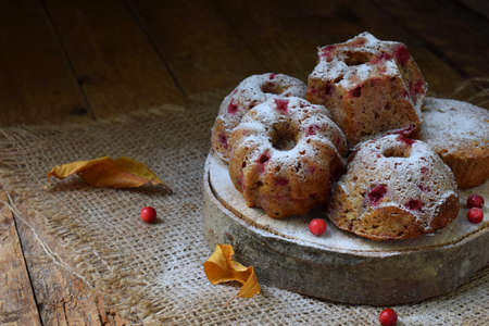 Muffins from oat and flax seeds with lingonberry on a cutting wooden background. Homemade baking. Gluten-free cake. Healthy pastries. Vegetarian food. Rustic photo. Copy space