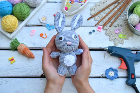 Making rabbit with carrot. Crochet bunny for child. On table threads, needles, hook, cotton yarn. Handmade crafts. DIY concept. Small business. Income from hobby
