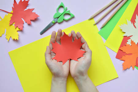 Making maple leaf from colored paper with your own hands for decoration of greeting card. Handmade crafts. Hello Autumn concept. Children's DIY. Copy space. Step 4. Done.