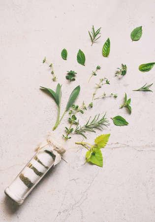 Ayurvedic herbal salt in glass jar. Sea salt with aromatic herb - rosemary, oregano, sage, marjoram basil, thyme, mint, bay leaf. Copy space. Zdjęcie Seryjne