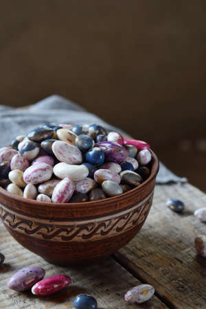Assortment of young legumes and beans of different varieties and colors in a clay bowl. Raw food. Healthy diet concept. Selective focus.