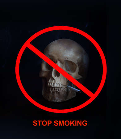 Human skull with a cigarette in teeth on dark background. Stop smoking concept. Nicotine addiction and bad habits.