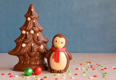 Chocolate Christmas tree and penguin on blue background. Happy New Year and Merry Christmas concept. Copy space.