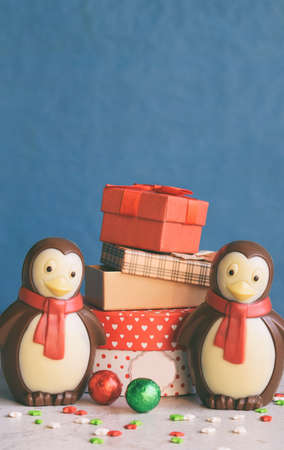 Chocolate penguin and gifts on blue background. Happy New Year and Merry Christmas concept. Copy space.