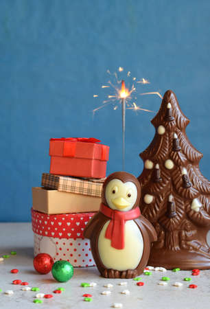 Chocolate Christmas tree, gifts and penguin on blue background. Happy New Year and Merry Christmas concept. Copy space. Stock Photo