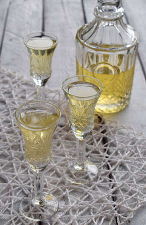 Ginger tincture or ale on wooden background. Spice yellow liqueur in a glass. Homemade Alcohol drink. Rustic style
