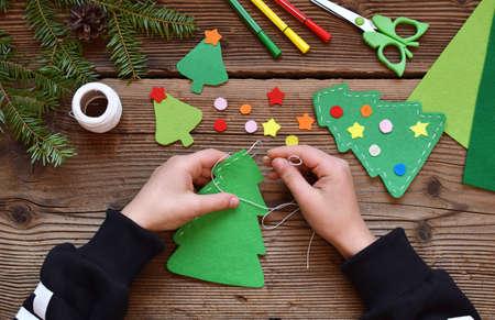 Fabricación de árbol de Navidad hecho a mano de fieltro con sus propias manos. Concepto de bricolaje para niños. Hacer decoración de juguetes navideños o tarjetas de felicitación. Foto de archivo