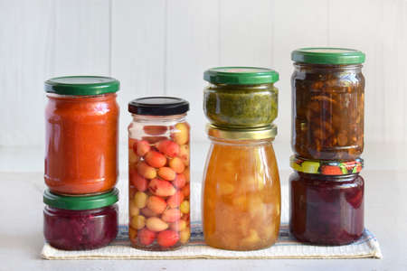 Variety of preserved food in glass jars - pickles, jam, marmalade, sauces, ketchup. Preserving vegetables and fruits. Fermented food. Autumn canning. Conservation of harvest.