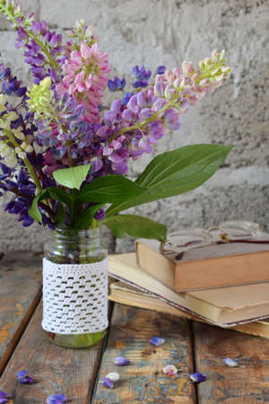 Pink, purple lupine flowers bouquet in vase and old book. Birthday, Mother's day, Valentine's Day, March 8, Wedding card or invitation. Festive Floral decorative background. Copy space.