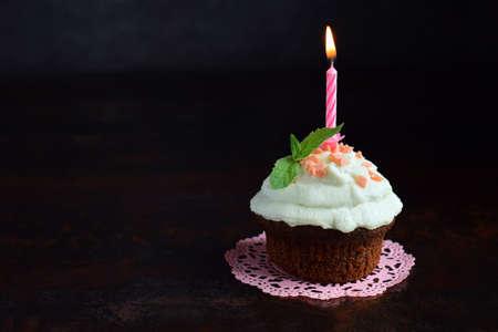 Chocolate cupcake with vanilla cream and candle. Happy Birthday. Dark photo. 免版税图像