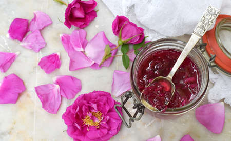 Jam of tea rose petal in glass jar on light marble background. Flower confiture. Healthy food. Copy space.