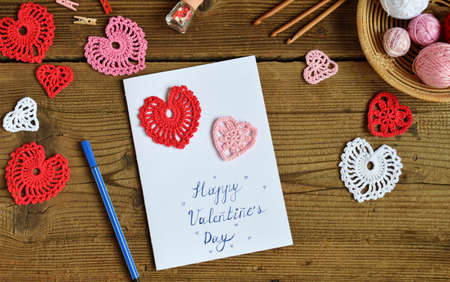 Making of handmade Valentine greeting card with crochet openwork hearts. Making of handmade decoration. Valentines Day crafts. Childrens DIY, hobby concept, gift with your own hands