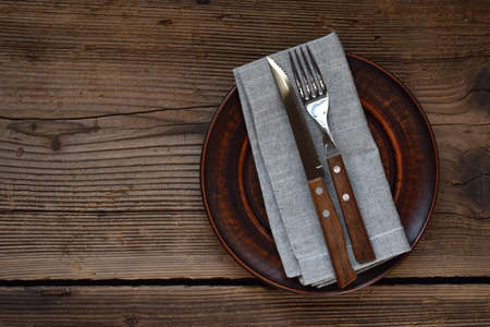 Empty clay plate, cutlery, napkin on wooden background. Table setting captured from above. Top view, flat lay. Rustic style. Copy space. Mock up, concept for restaurant, menu. Imagens
