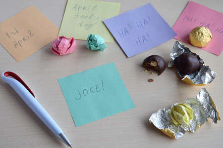 April fools day prank. Wrapping hazelnut in candy wrappers on wooden table. Joke with food