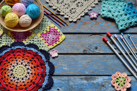 Equipment for knitting and crochet hook, colorful rainbow cotton yarn, ball of threads, wool, knitted elements, napkin . Granny square. Handmade crocheting crafts. DIY concept. Copy space. Archivio Fotografico