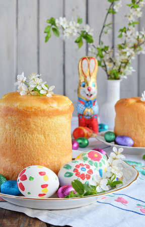 Happy Easter concept. Sweet bread with dried fruits and colored eggs. Holidays breakfast. Orthodox kulich. Festive table place setting decoration with paska, blossom twigs, bunny, chocolate egg