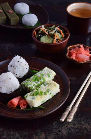 Mix of Japanese food - rice balls onigiri, omelette, ginger, sunomono wakame cucumber salad. Traditional dessert of bean and green tea matcha - jelly yokan, daifuku mochi. Asian breakfast or lunch.