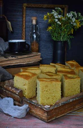 Homemade corn cake with tangerines on dark background. Traditional Brazilian sweet pie. Cornbread. Style Dark Moody 스톡 콘텐츠