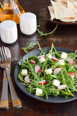 Salad of fresh vegetables - arugula, radish, feta cheese in black plate with flat bread tortilla. Healthy food.