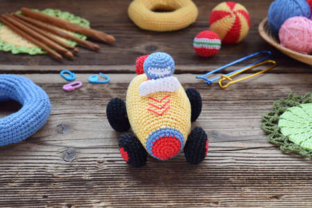 Making colored crochet racing car. Toy for babies and toddlers to learn mechanical skills and colors. On the table threads, needles, hook, cotton yarn. Handmade crafts. DIY concept Standard-Bild