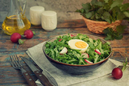 Vitamin salad from lettuce, radish, green onions and eggs, seasoned with vegetable oil in plate on wooden background. Healthy food. Salad of fresh green vegetables. 스톡 콘텐츠