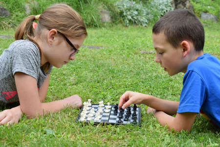 The Girl and boy playing chess outdoors. Children lie on green grass in summer park. Happy childhood 写真素材