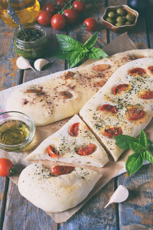 Traditional Italian Focaccia with tomatoes, basil, garlic and sumach. Homemade pastry. Flat bread. The organic flatbread. Rustic style
