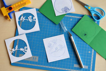 Making tunnelbook. The 3D greeting card Spring. Artwork equipment and tools for paper cut - cutting knife, sharp box cutter, blue cutting plate, origami paper. Modern 3d origami paper art style.