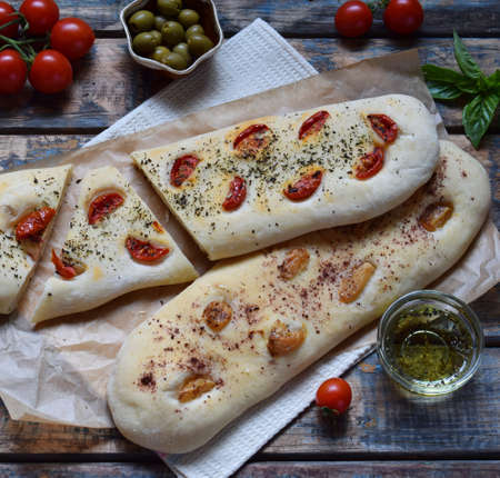The traditional Italian Focaccia with tomatoes, basil, garlic and sumach. Homemade pastry. Flat bread. Organic flatbread. Rustic style Imagens