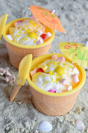 The homemade vanilla ice cream on yellow sand summer beach. White frozen delicious dessert in individual jello vase. Reklamní fotografie