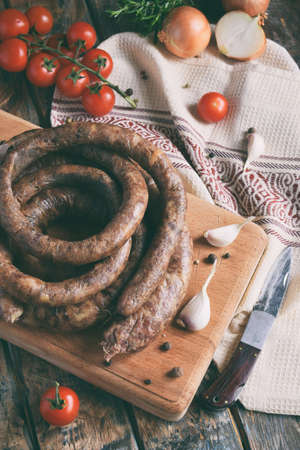 The traditional smoked sausage ring in a rustic style. Appetizing sausages made of pork and lamb with fresh herbs, spices on the wooden board. Free space for text. Imagens