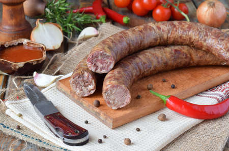 The traditional smoked sausage in a rustic style. Appetizing sausages made of pork and lamb with fresh herbs, spices on the wooden board. Free space for text. Imagens